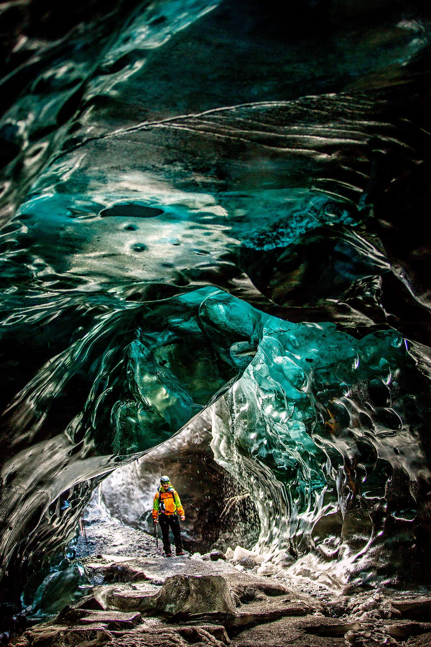 ©KontraPixel – woman standing in a massive ice cave