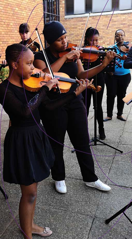 Young violinists perform together in the Johannesburg Youth Orchestra Company (JYOC)