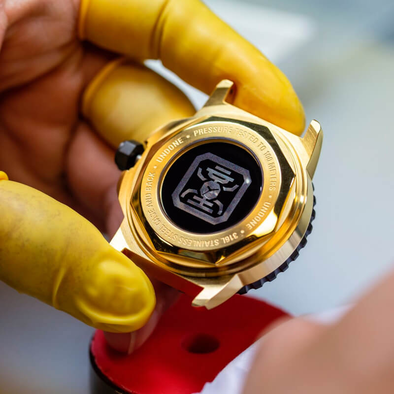 A customized watch with a customized caseback being held by a man