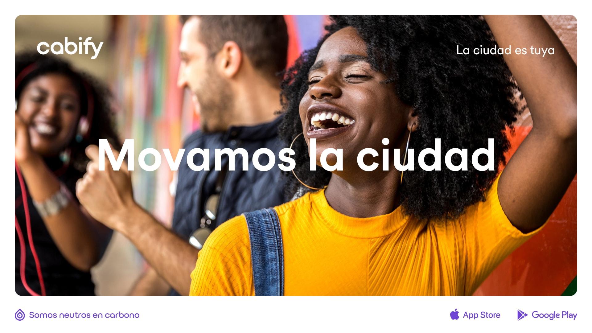"""Un anuncio con la imagen de una mujer contenta y el texto """"Movamos la ciudad"""""""