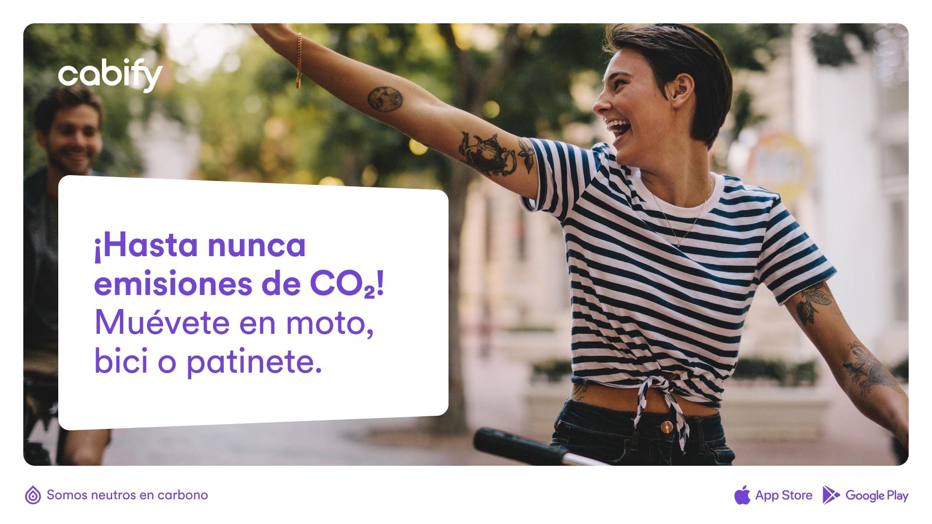 """Un anuncio con una foto de una chica en bici y el texto """"Hasta nueva emisiones de CO2. Múevete en moto, bici o patinete."""