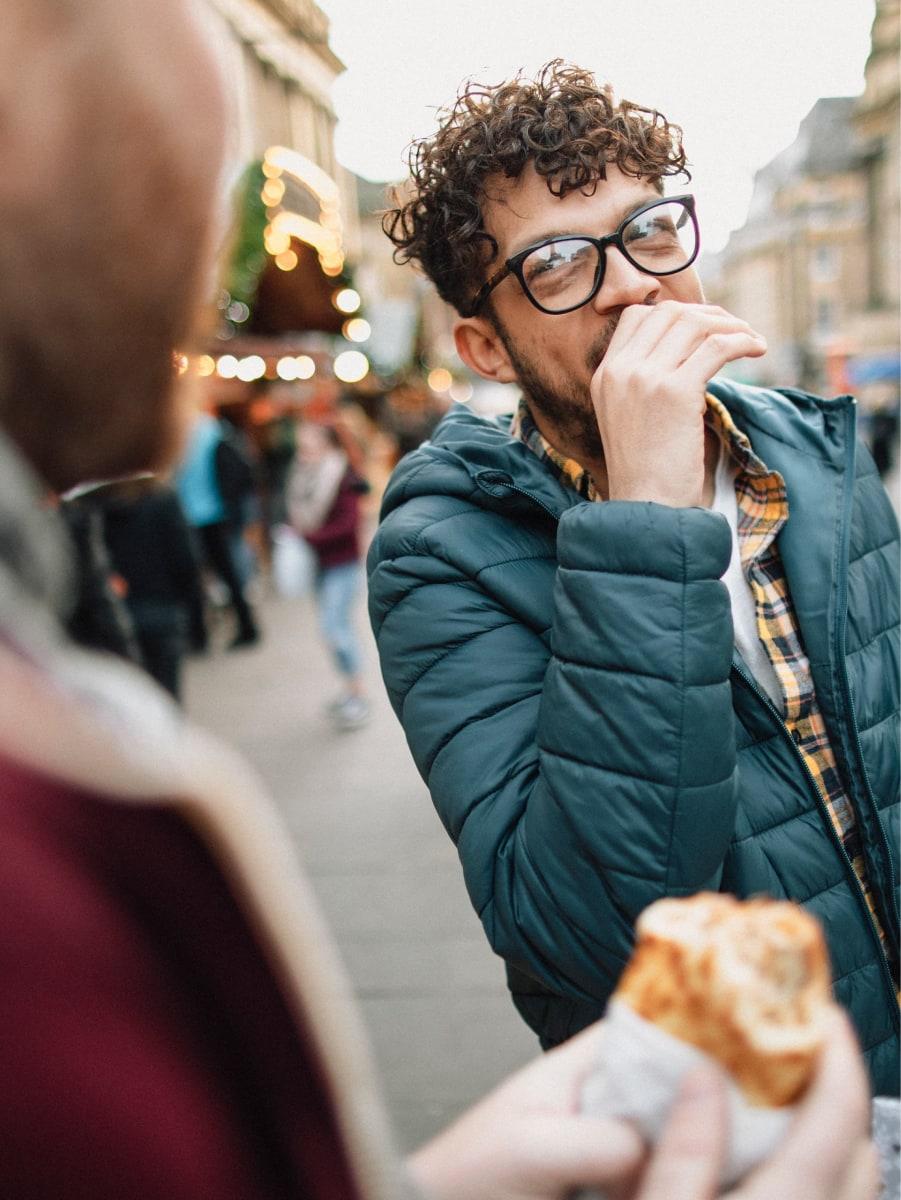 Dos chicos comiendo en la calle