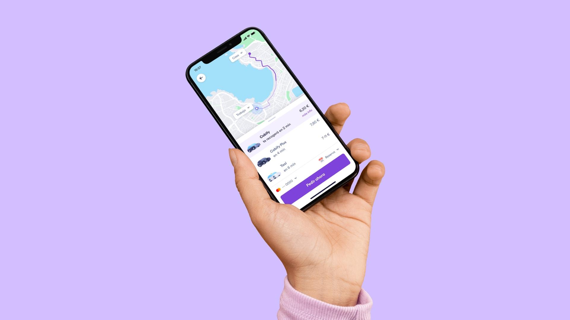 Una mano sostiene un móvil con la app de Cabify