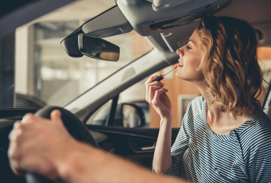 Una mujer que se maquilla en un coche