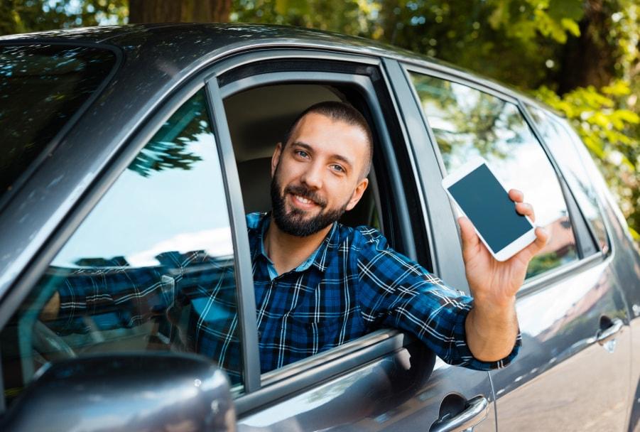 Un conductor mostrando su móvil por la ventanilla