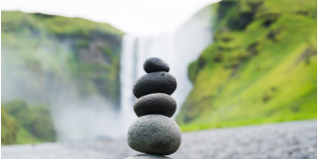 Stacked rocks in front of water fall