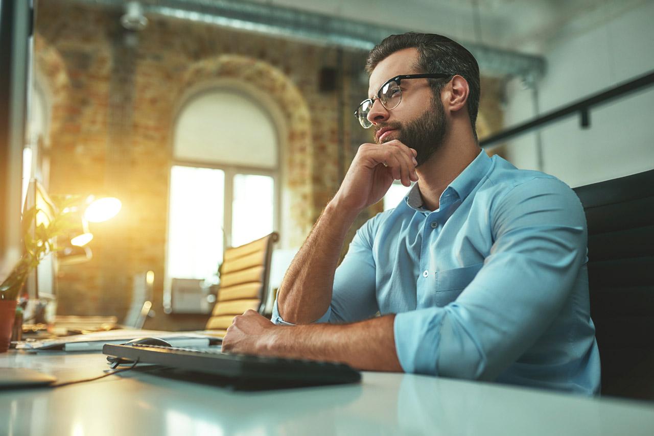 homem refletindo em frente ao notebook