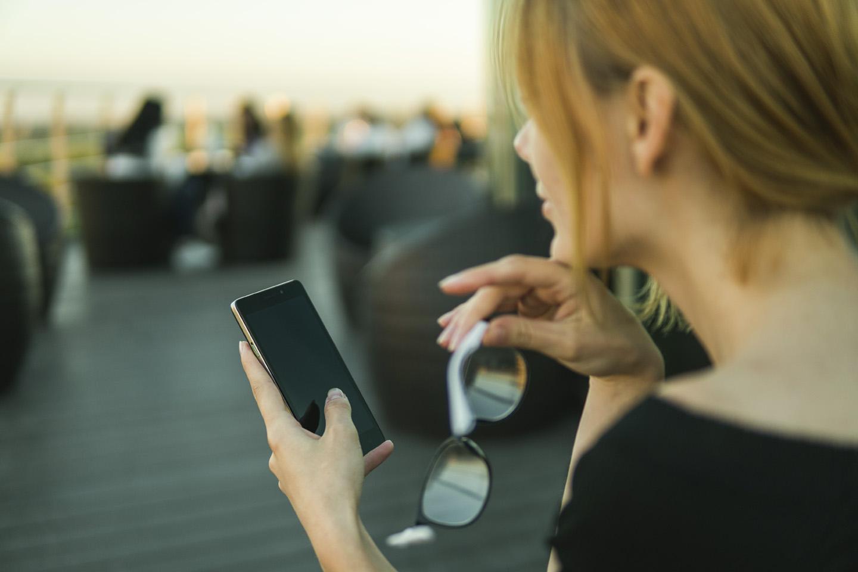 mulher usando o celular segurando os oculos