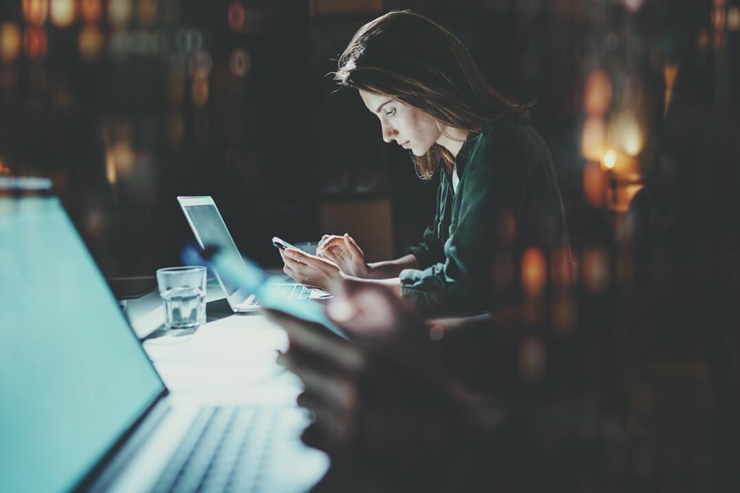 mulher usando o smartphone em um ambiente escuro
