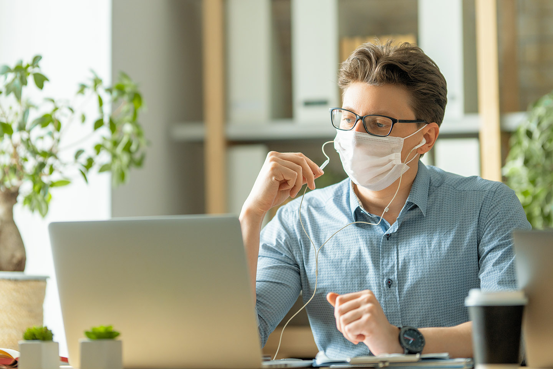 homem de mascara trabalhando no notebook