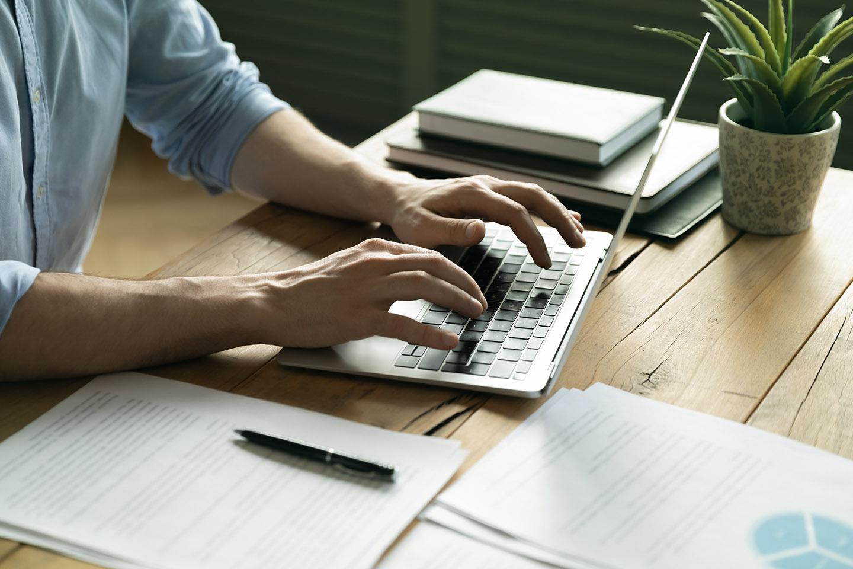 homem trabalhando no notebook com documento sobre sua mesa
