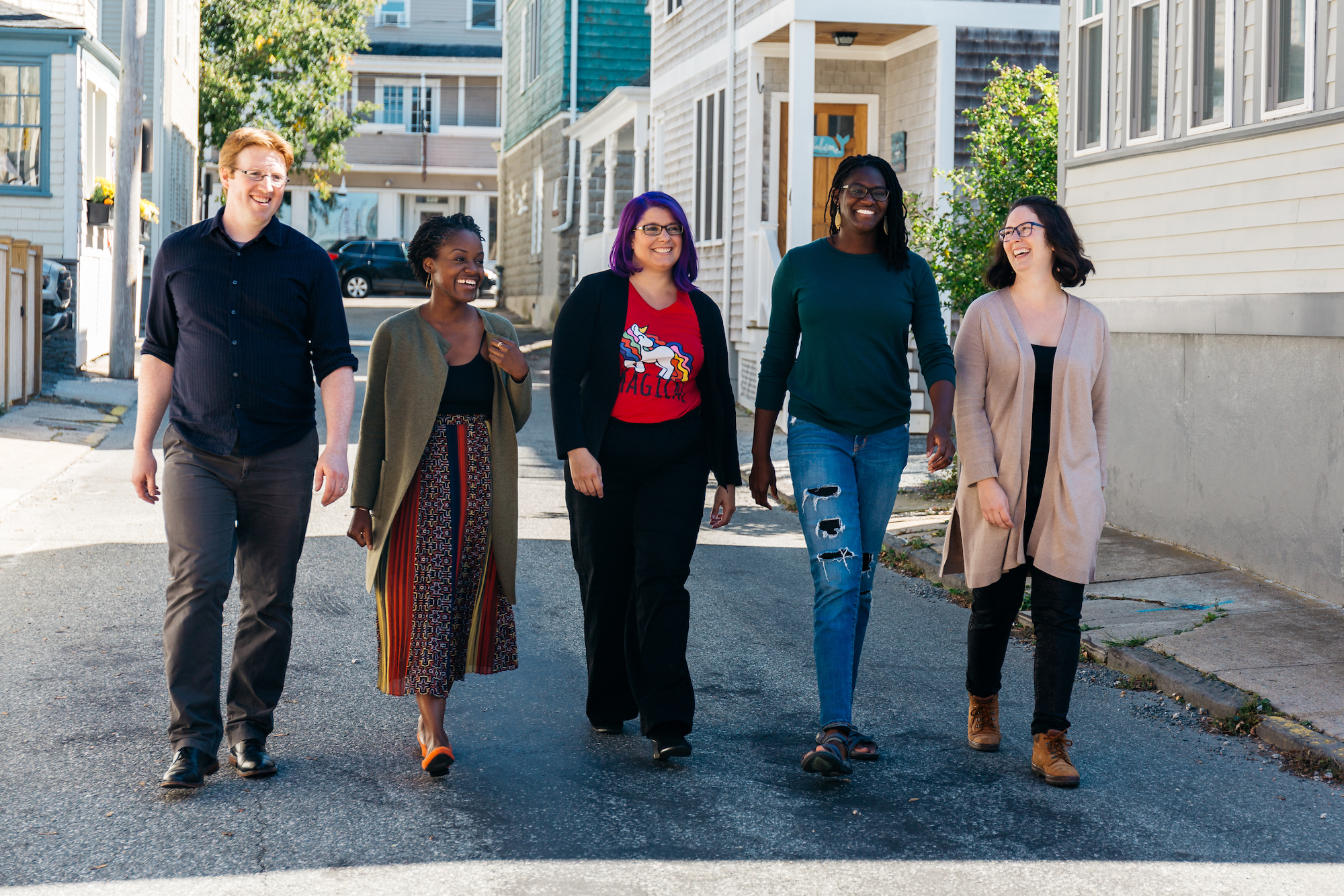 5 members of the Pixels for Humans team and partners walking down a sunny street with confidence. From left to right: Jim ONeill, Tricia Douglas, Heather ONeill, Hailey Thomas, and Melanie Scroggins.
