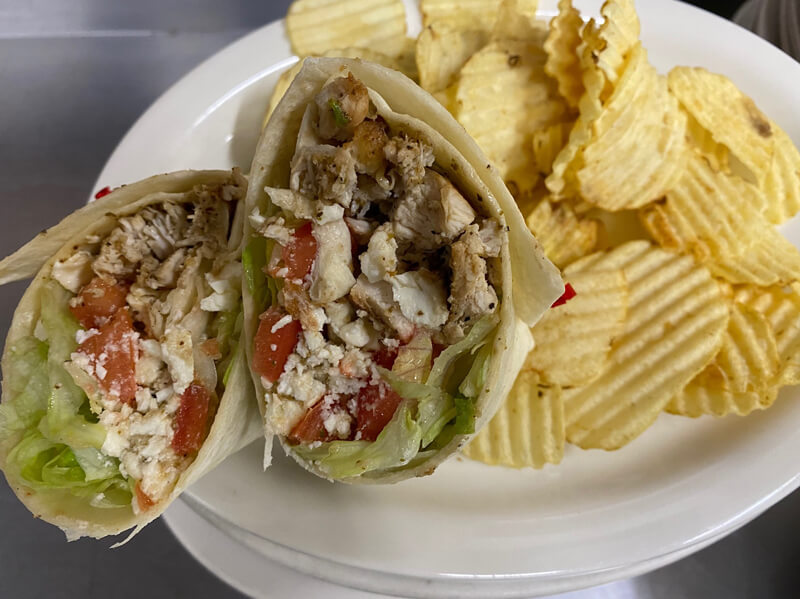 Greek chicken wrap with chips.