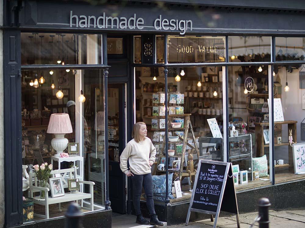 Handmade design shopkeeper standing outside her shop