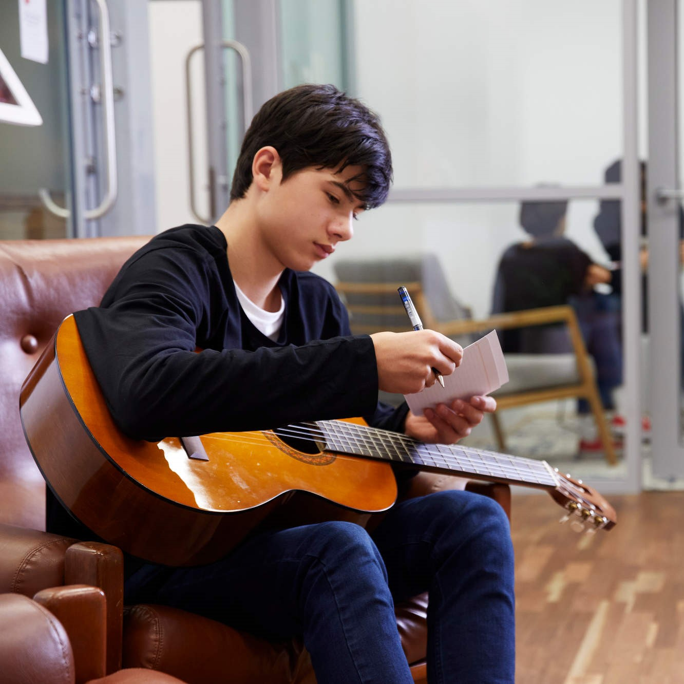 A teenage boy holding a guitar and smiling.