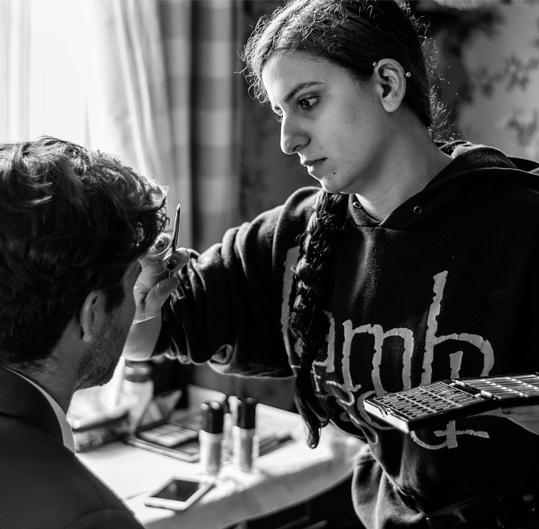 woman applies makeup on a film set.