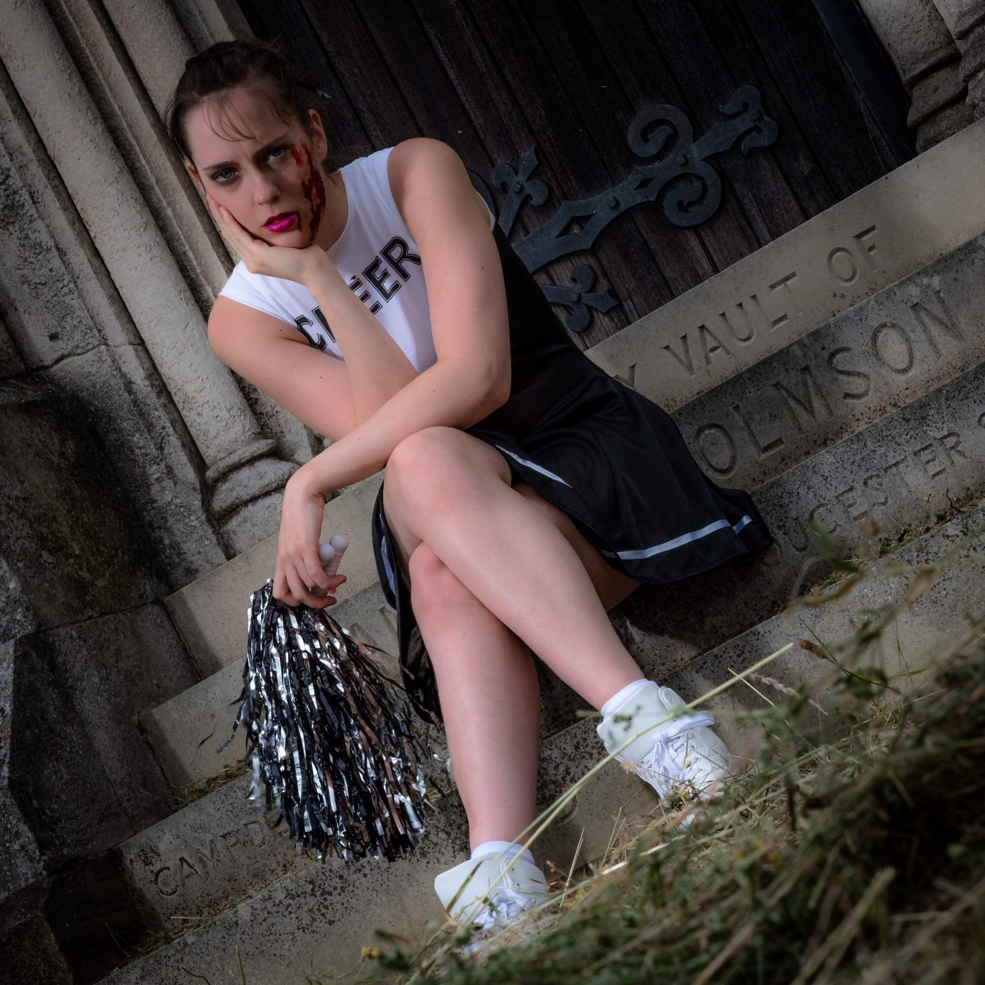 Horror makeup. A cheerleader with blood and scars sits on some steps.
