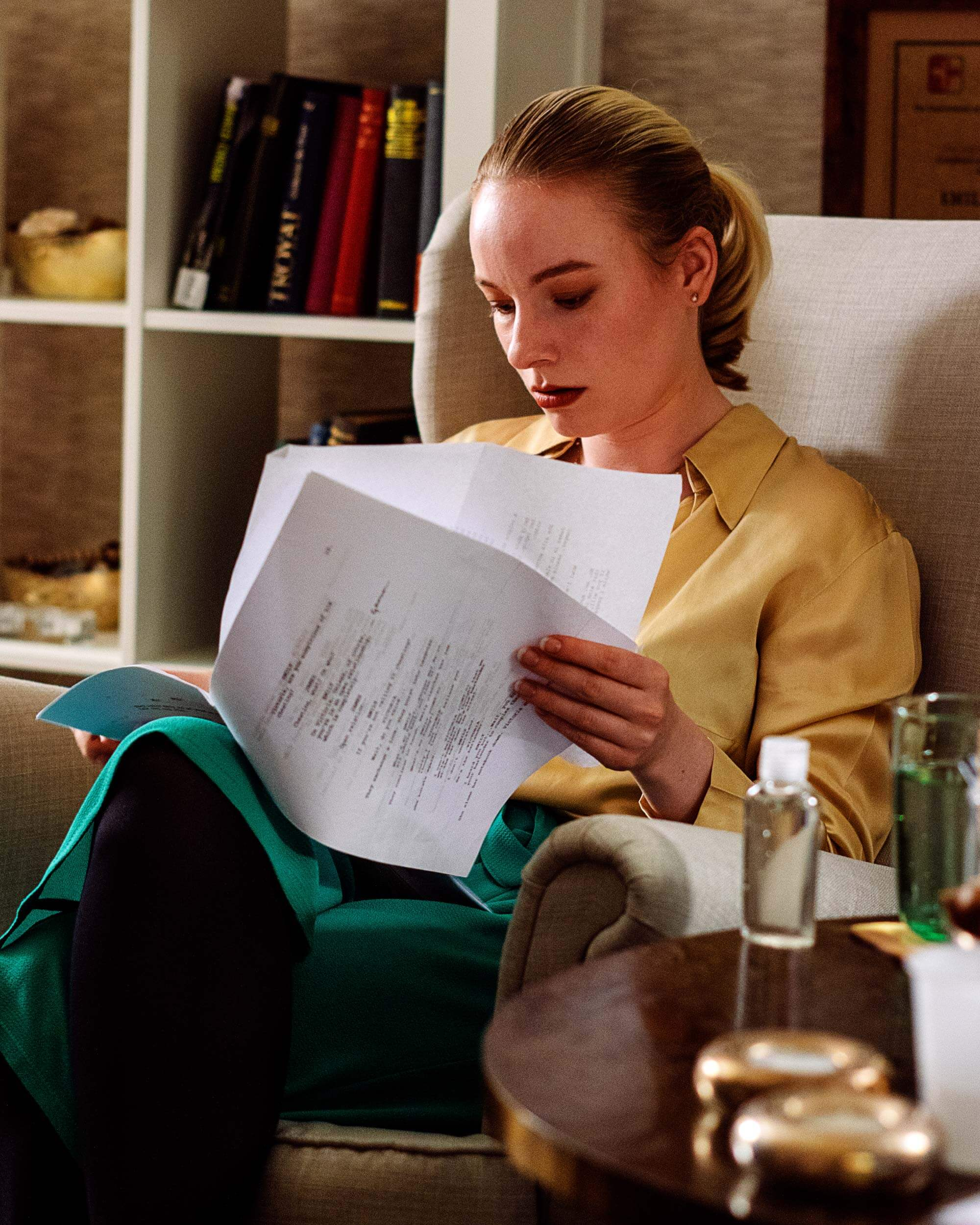 Woman in sitcom reads some papers in her living room.