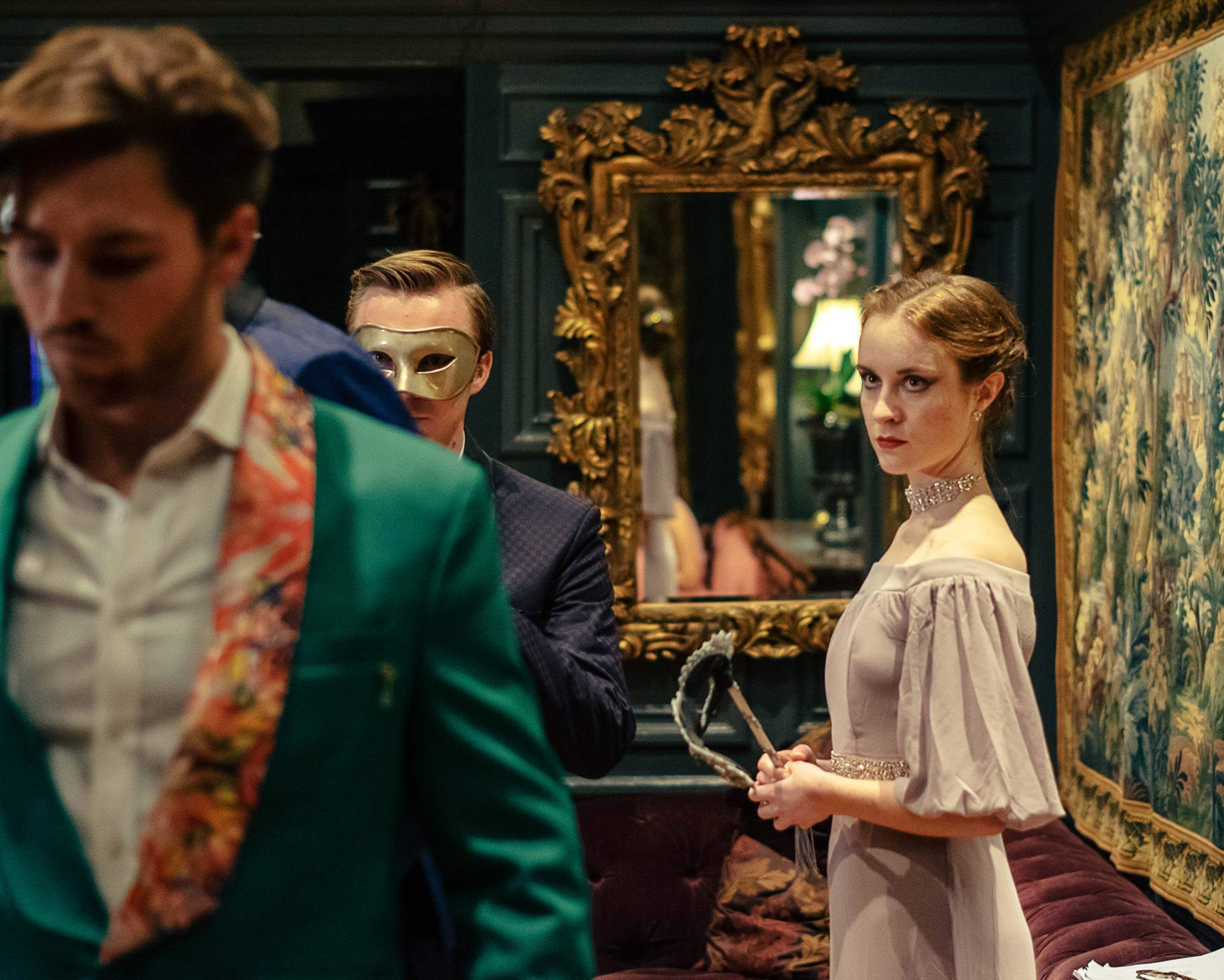 Professional makeup for a period drama. A man in a green jacket walks away from a woman.