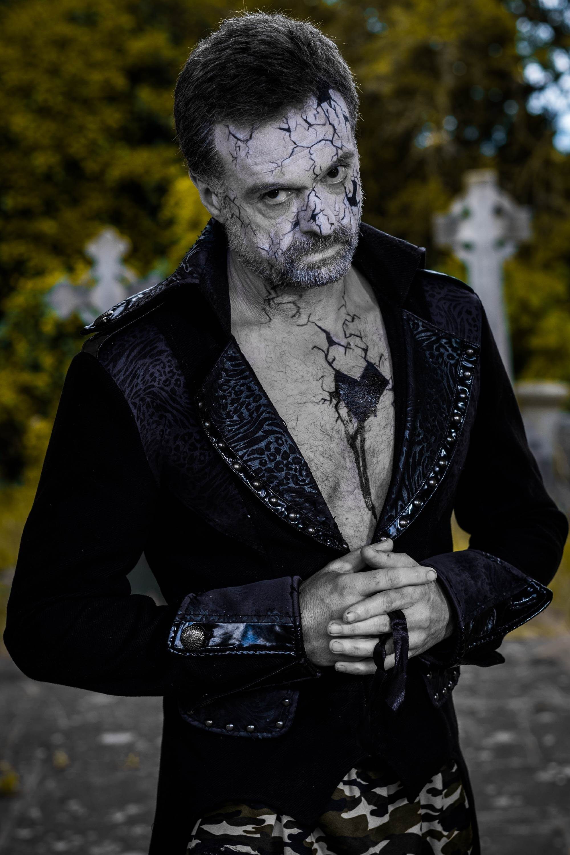Fantasy makeup. A man with elaborate white zombie makeup, wearing a suit jacket, poses for a photo in a park.