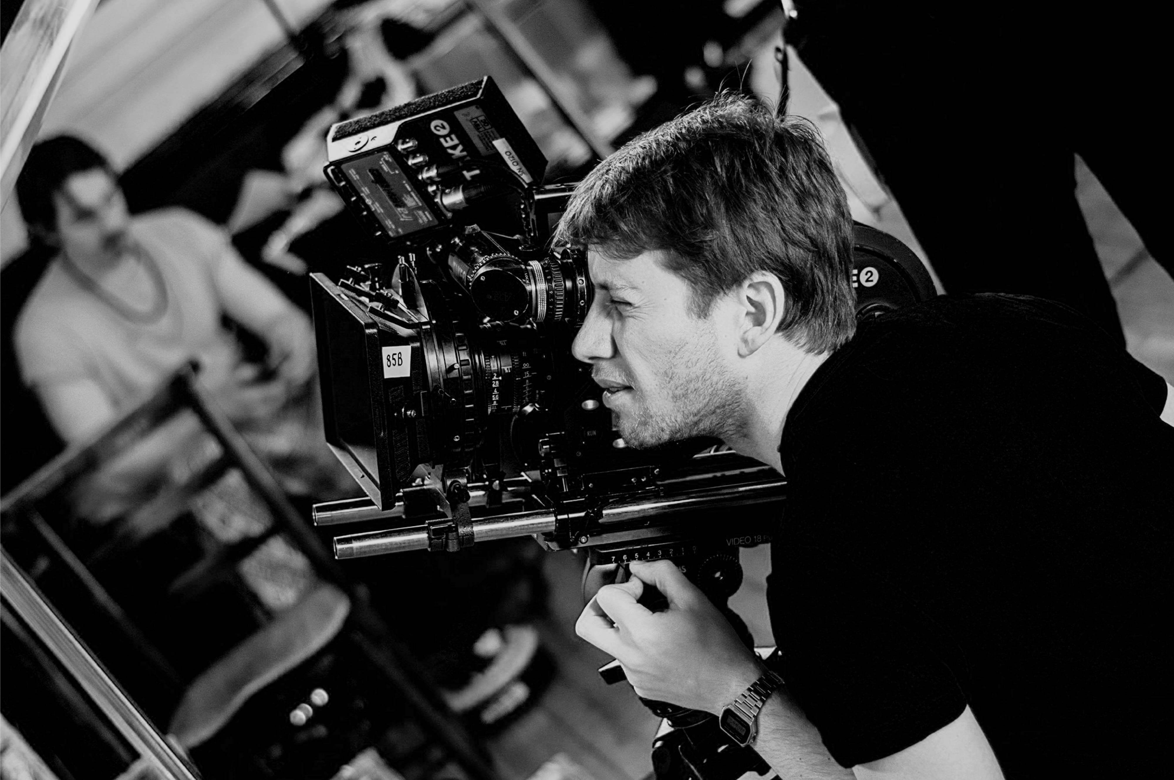 Behind the scenes of All Stretched Out, directed by Alistair Train and produced by Lunar Dragon. A man uses an analog film camera on film set.