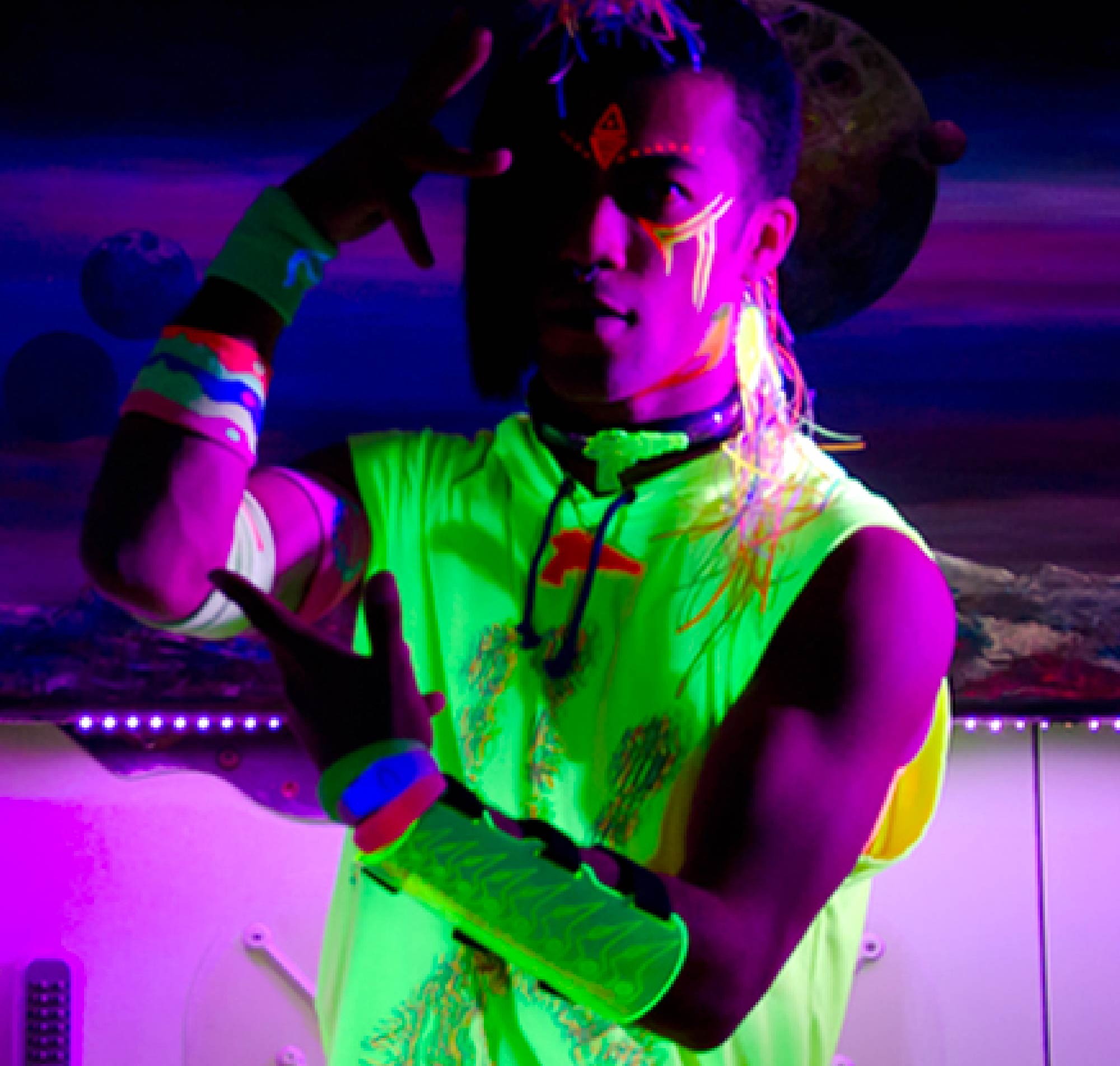 Makeup for London music video. Man with fluorescent clothes and paint poses under a blacklight.