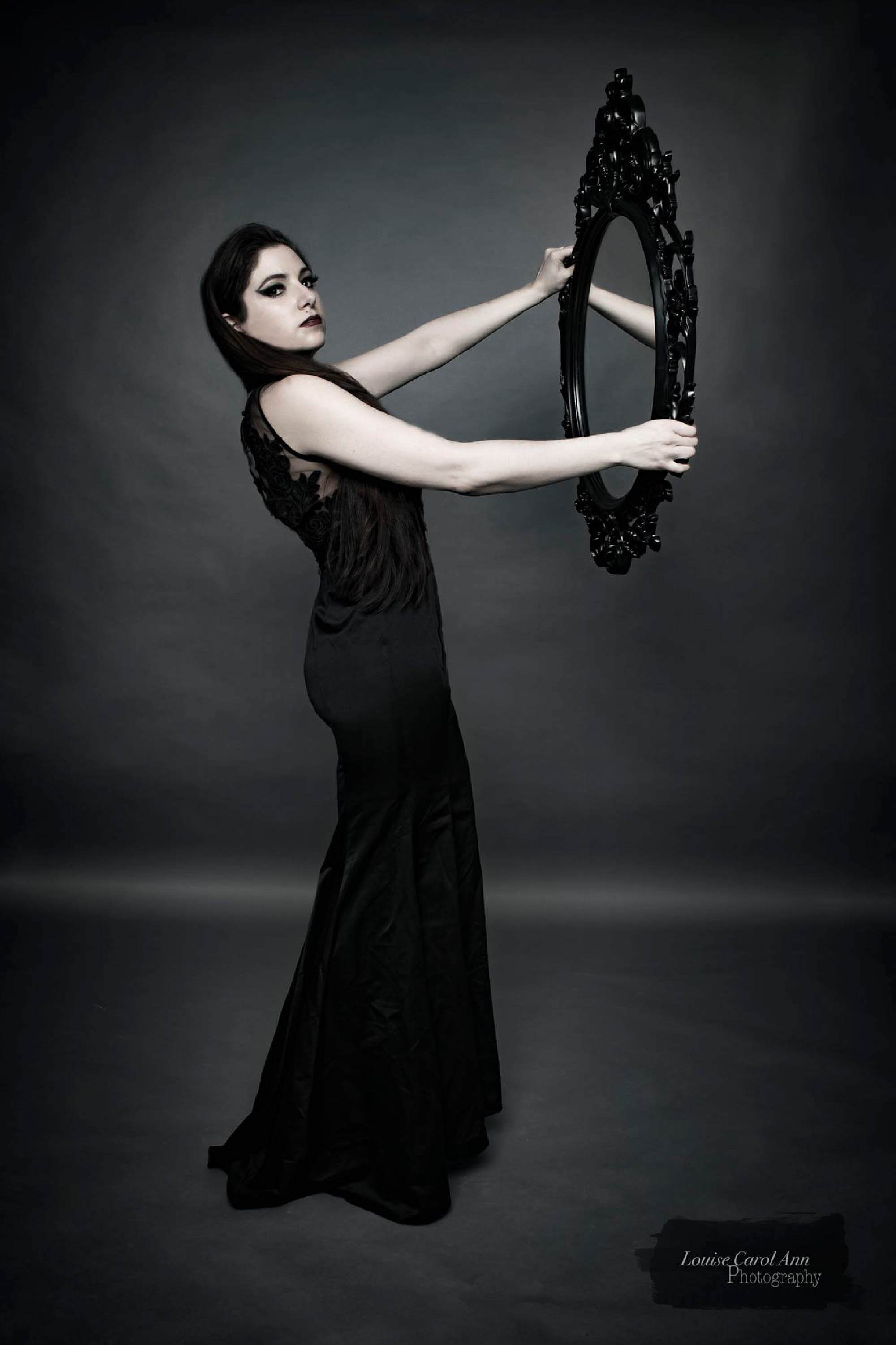 Woman in black dress holds up a mirror to herself.