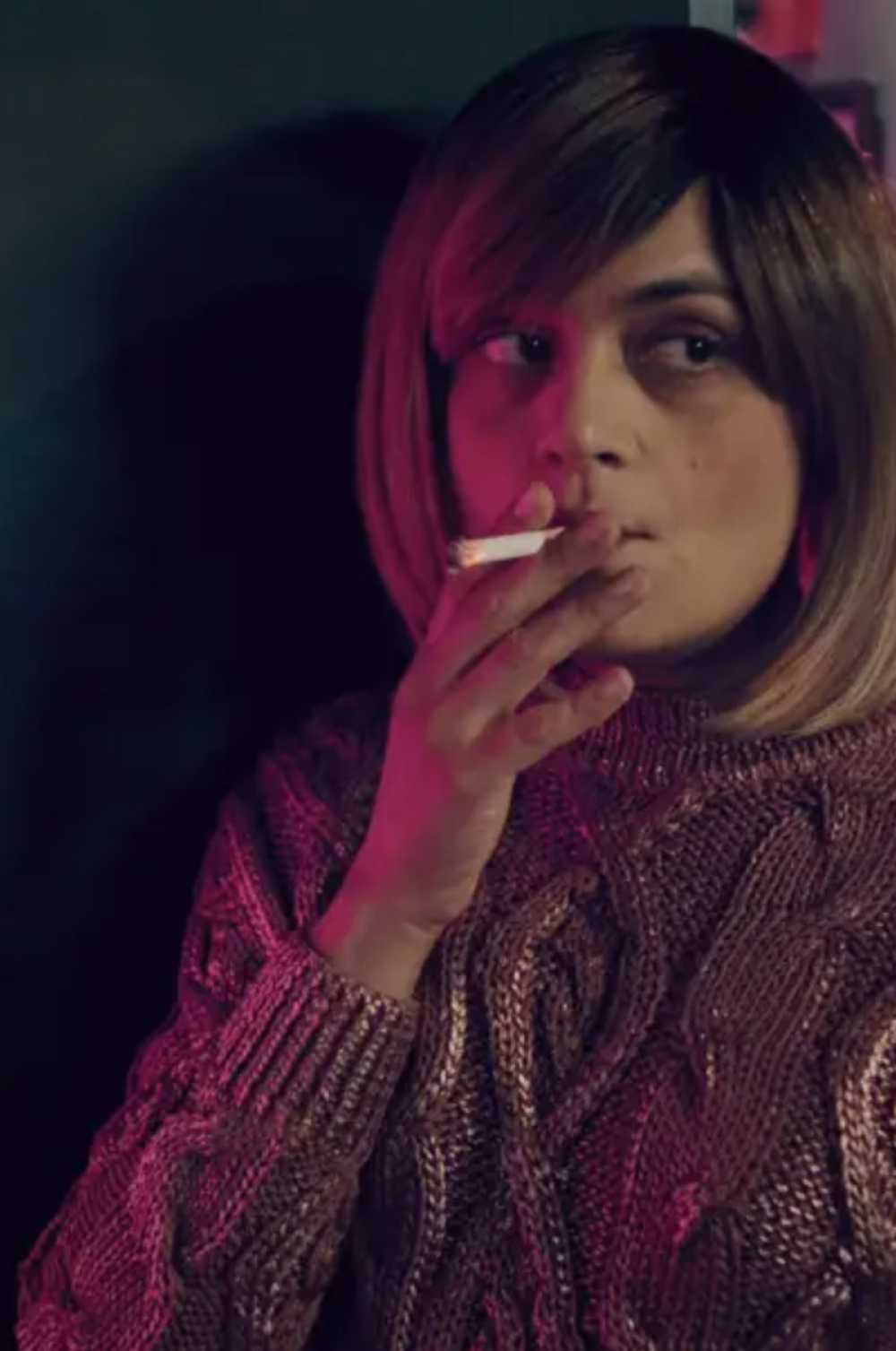 Girl drenched in pink light smokes a cigarette tentatively. Image from the film One Way Glass, produced by Lunar Dragon Productions.