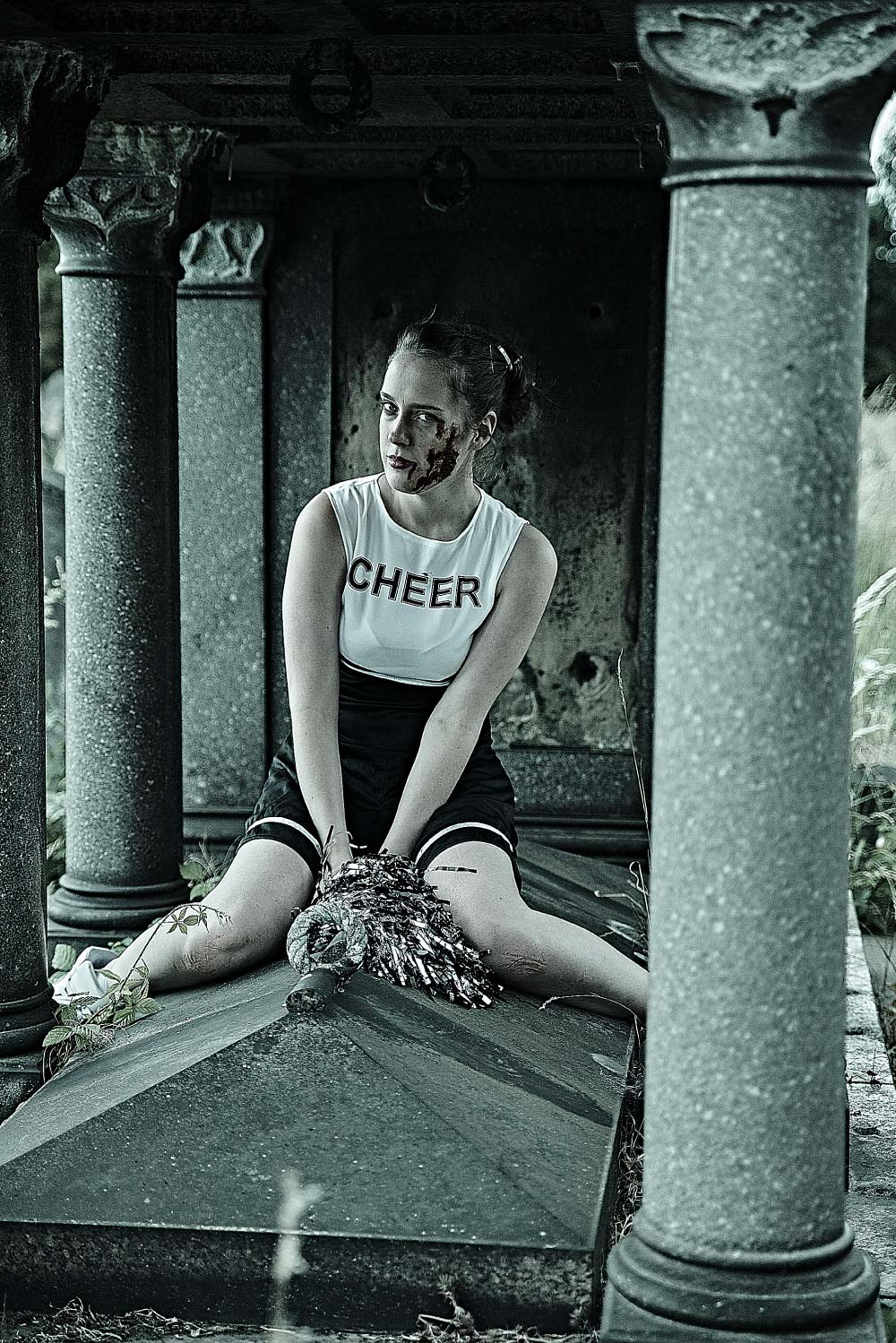 Horror makeup. A bloody and scarred cheerleader sits on top of a grave.