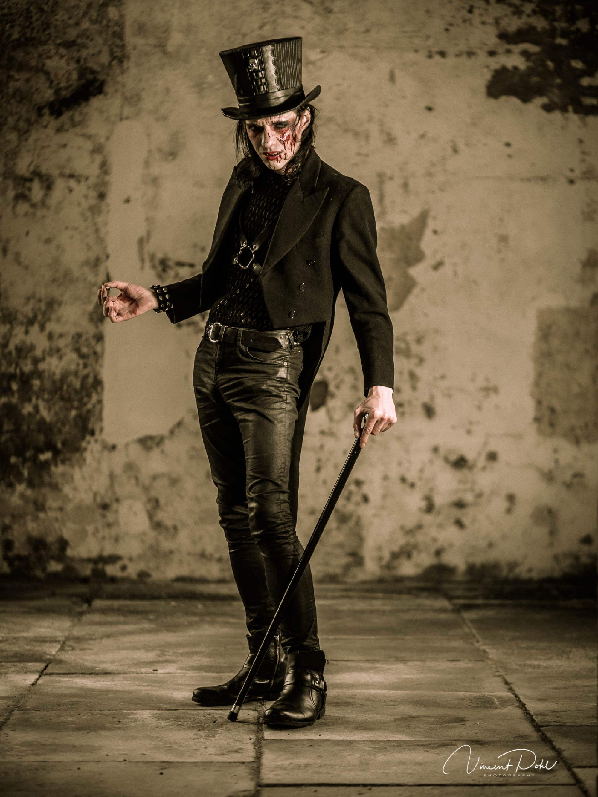 Fantasy makeup. A man with blood on his face, a top hat and a cane poses for a photo.