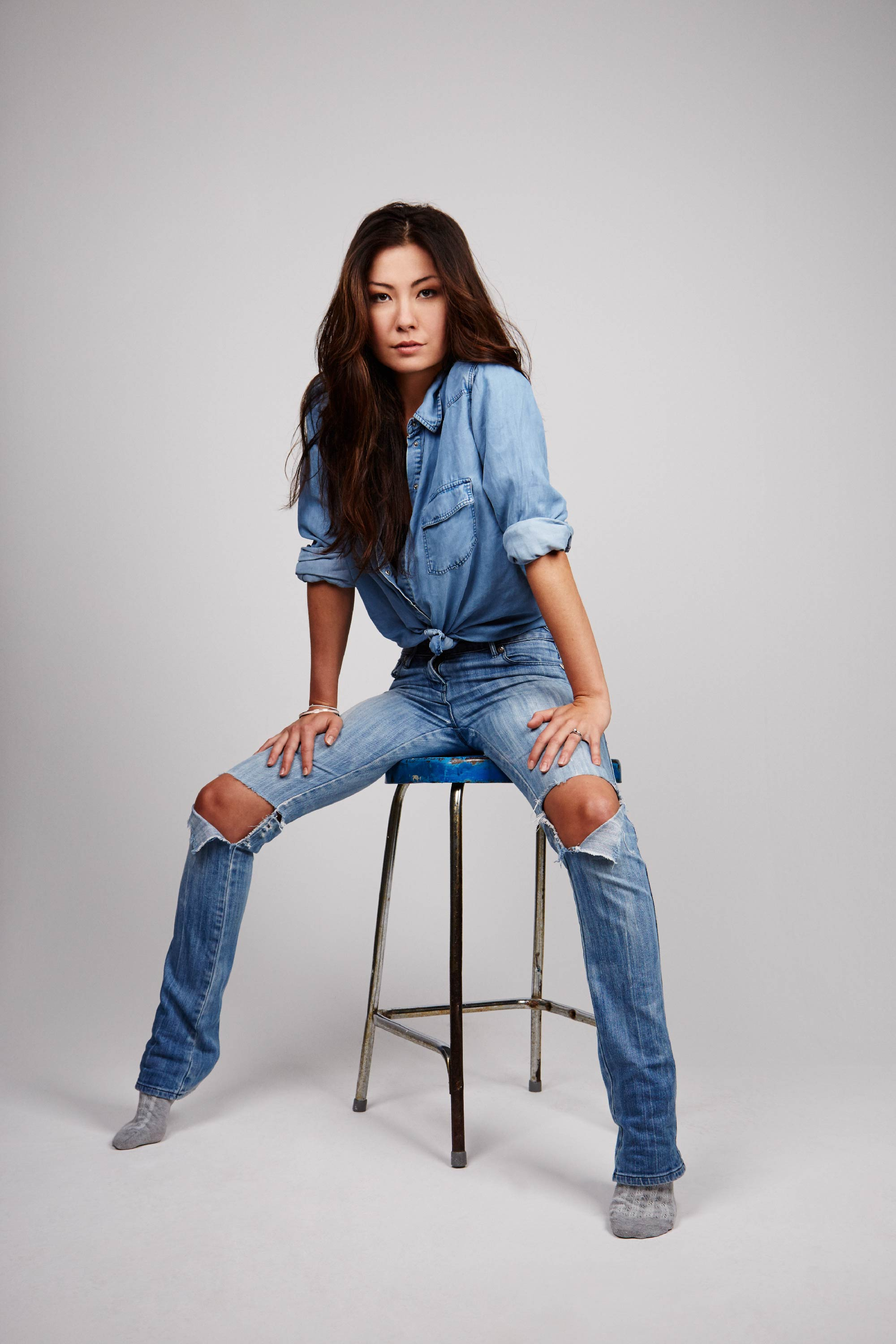 Makeup for London fashion shoot. Woman in double denim sits on top of stool.