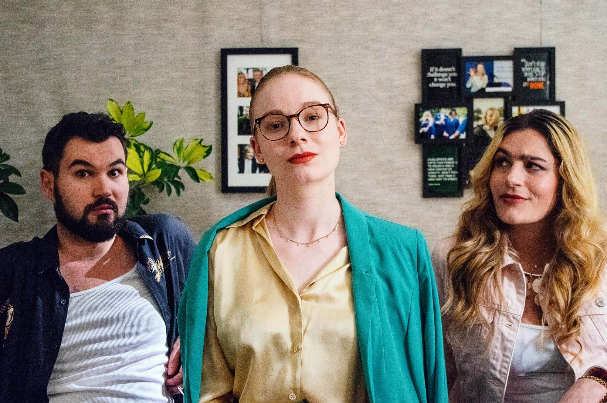 Three people pose in a living room. Professional sitcom makeup provided by Lunar Dragon.