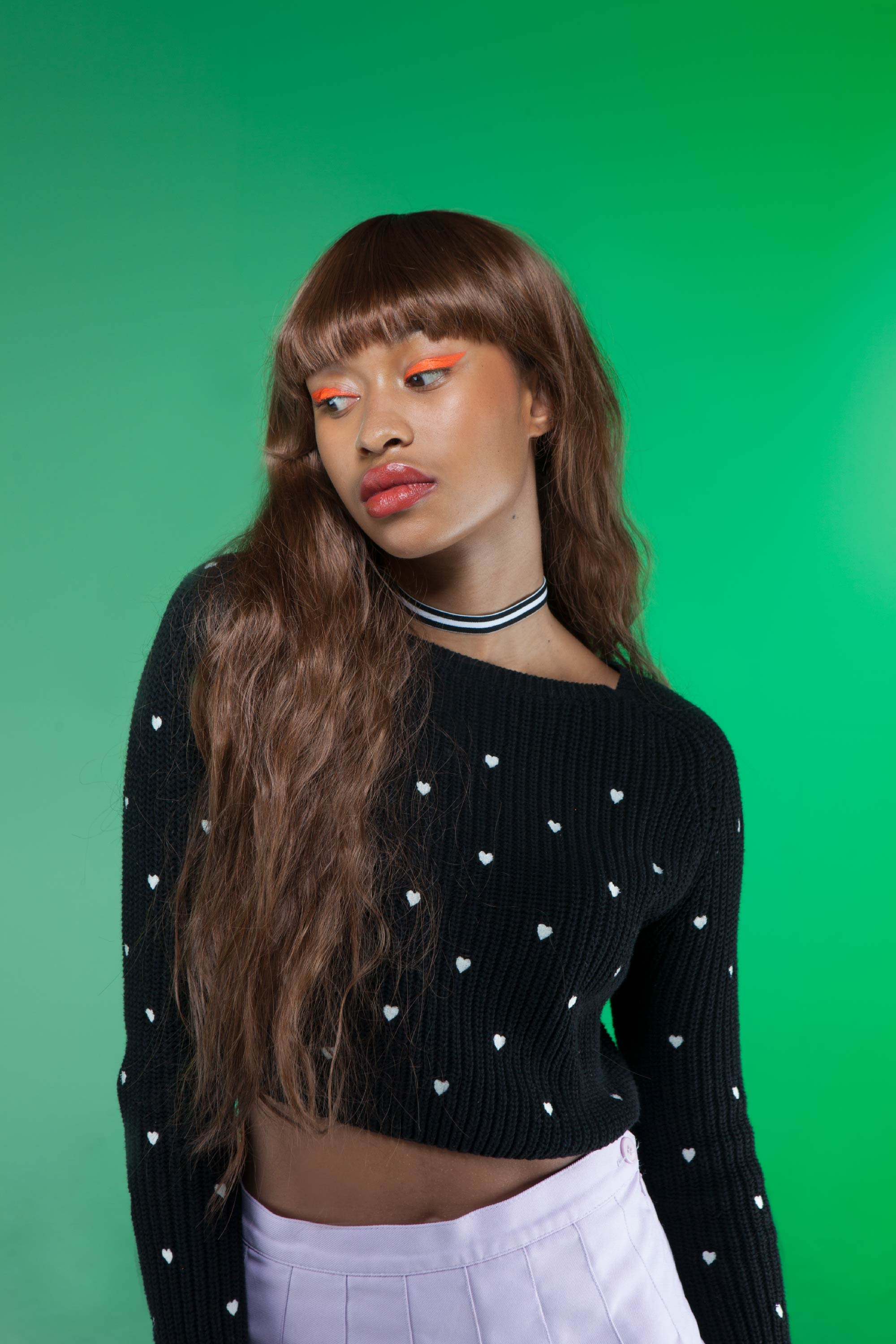 Makeup for profesional London photoshoot. Girl poses against a green studio background.