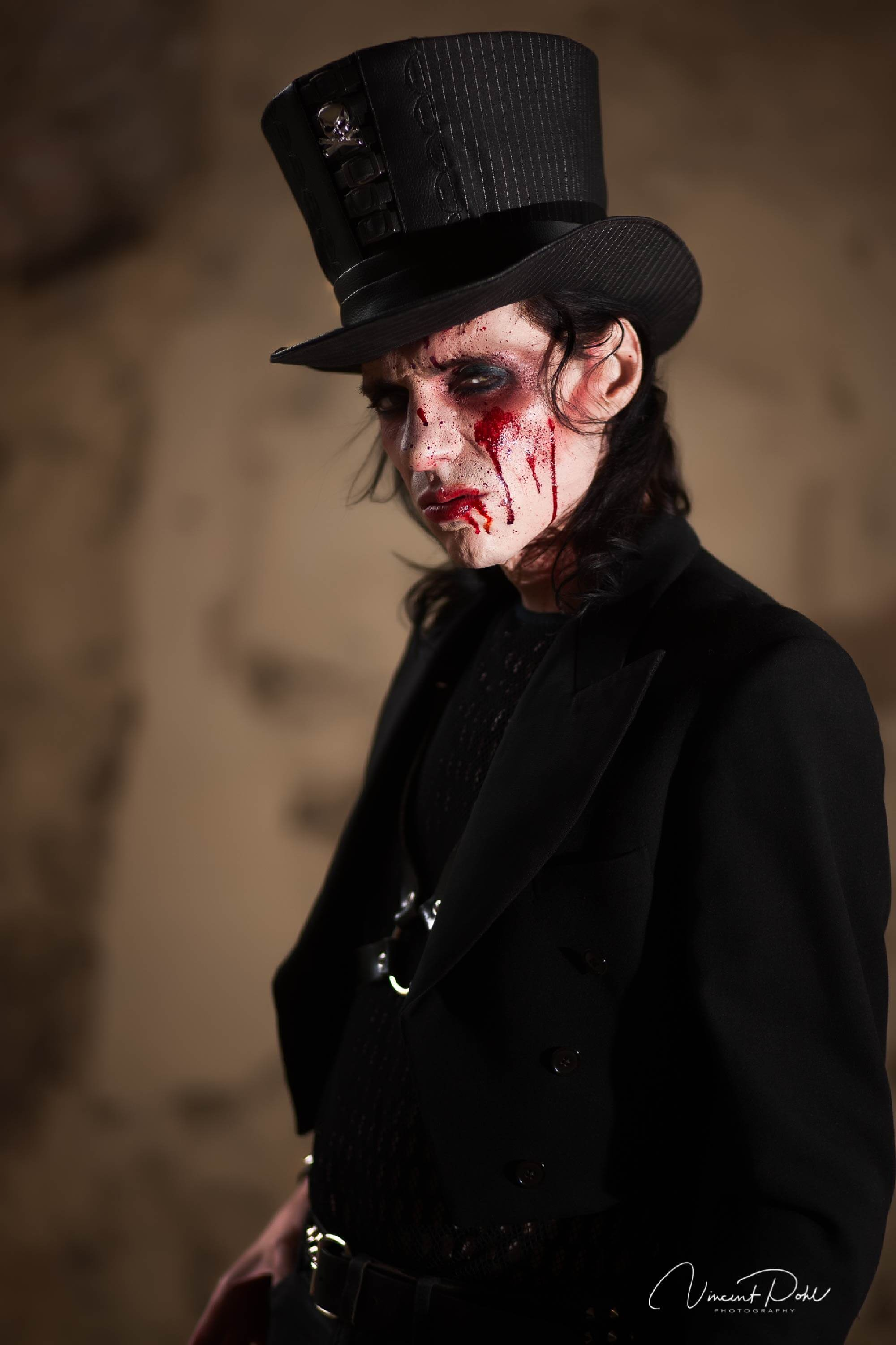 Fantasy makeup. A man with blood on his face and a top hat poses for a photo.