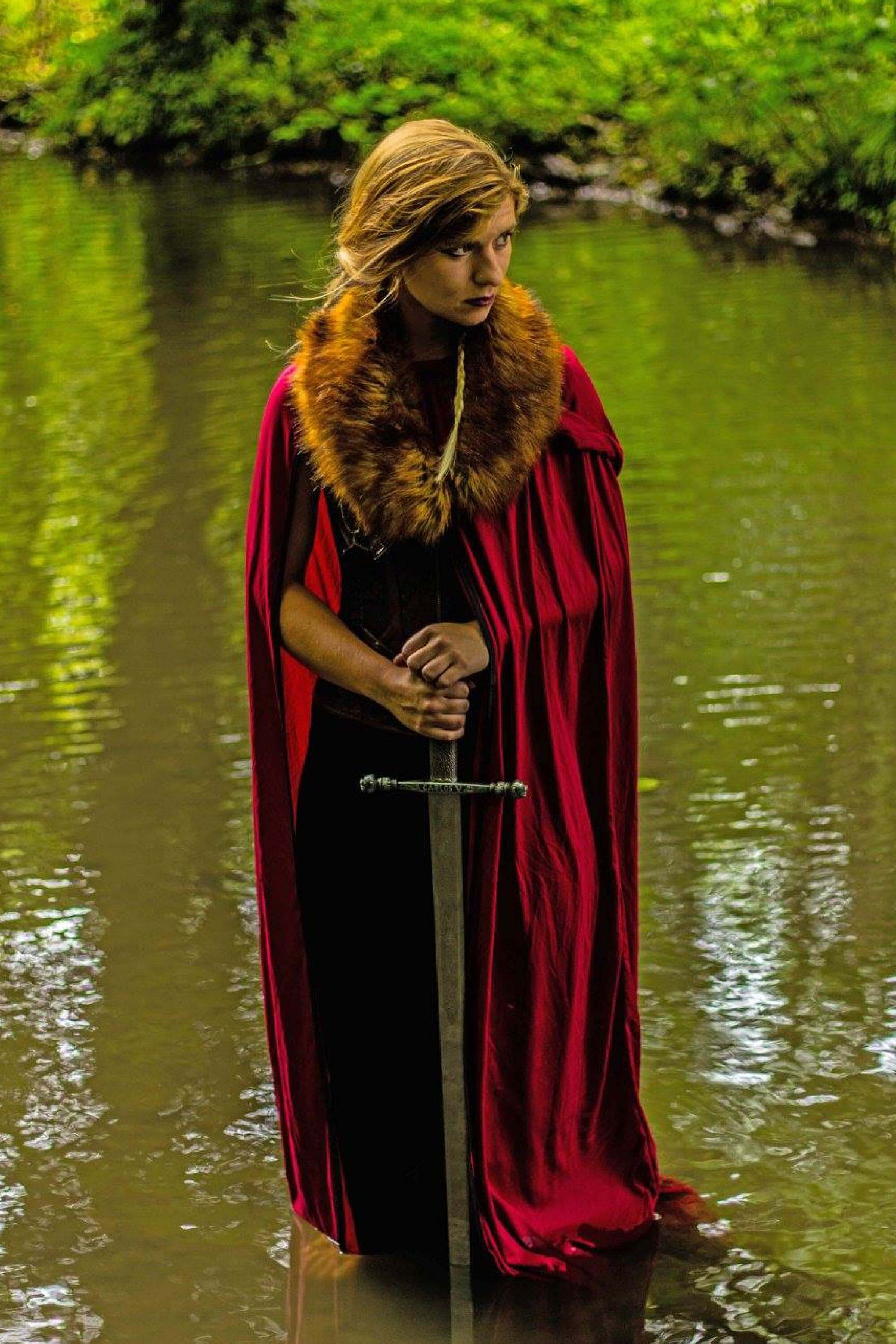 Woman in a red cloak holds a sword in a river