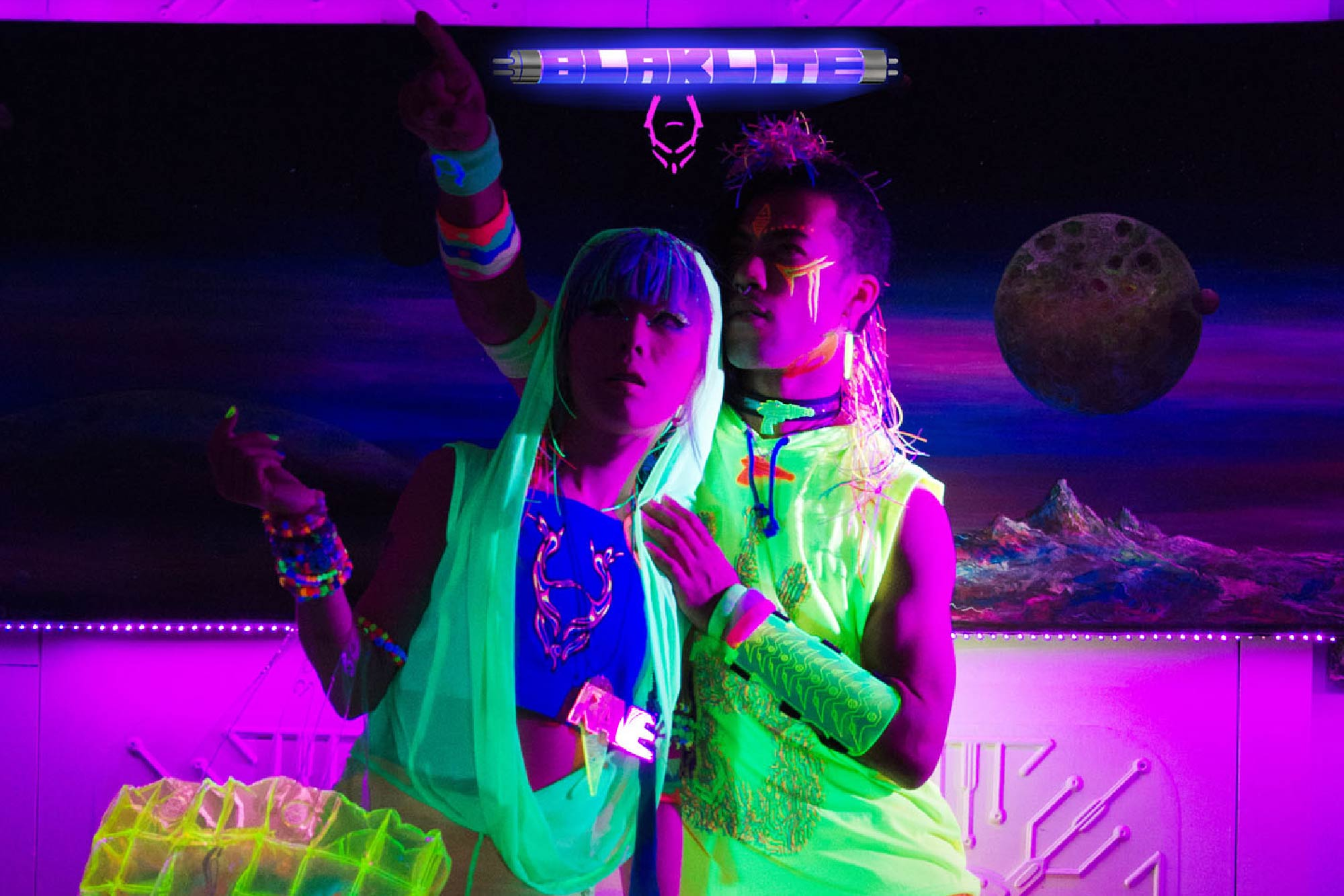 Music video production in London. Fluorescent electro steampunk couple pose under blacklight together.