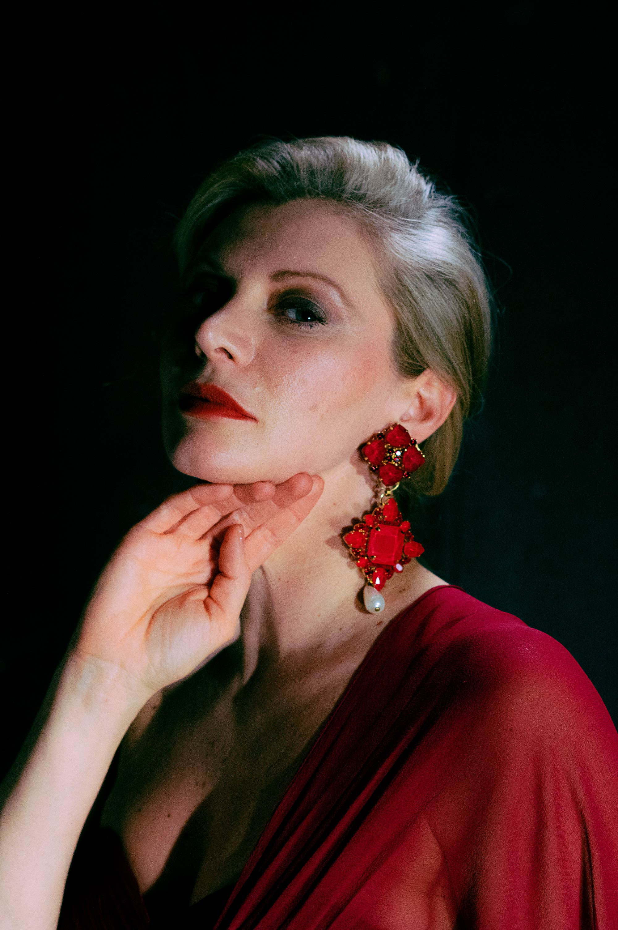Fashion makeup. Woman in red dress poses for fashion photography.