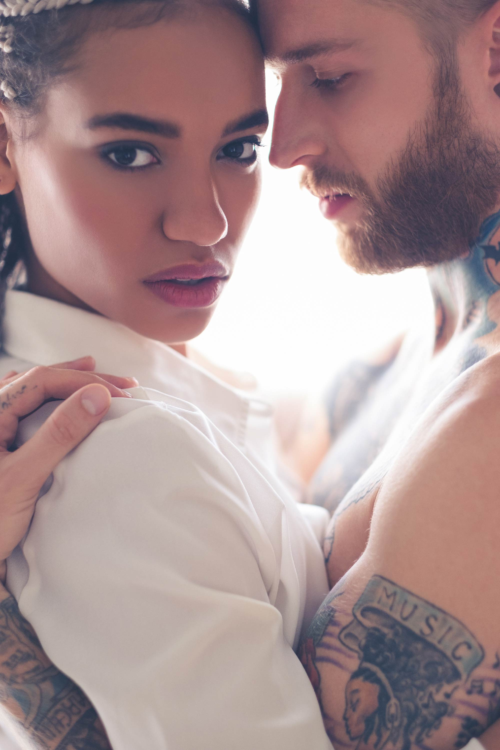 Makeup for London photoshoot. Tattooed man poses seductively with woman.