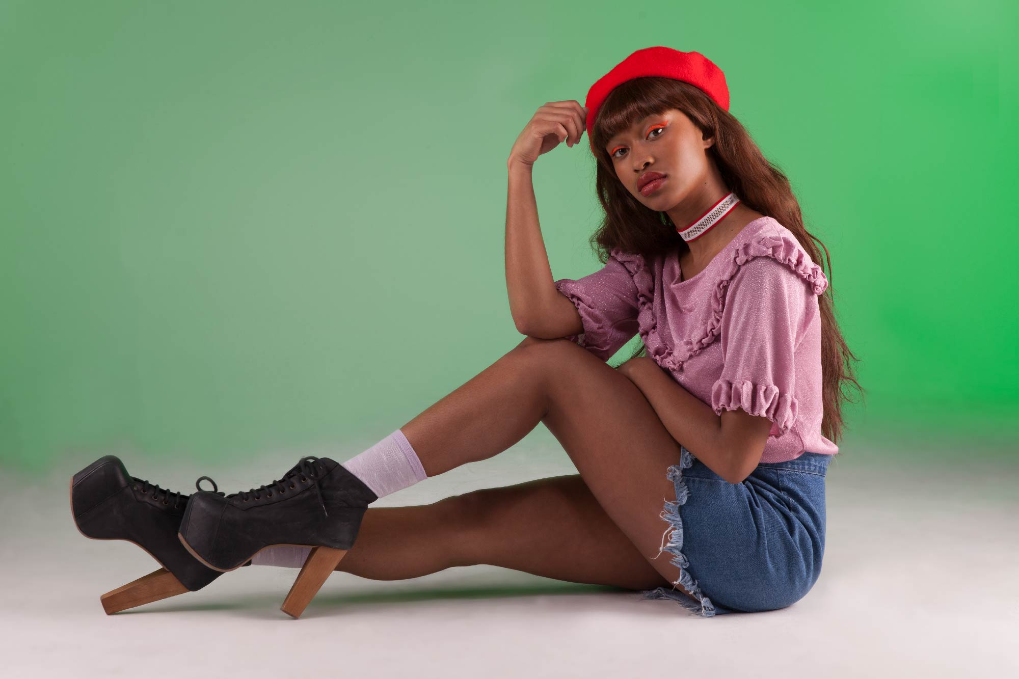Professional fashion shoot in london. Girl in red hat poses whilst sitting on the floor, with a green backdrop.