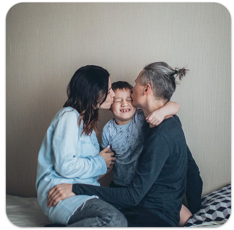 A family sitting together on a bed.