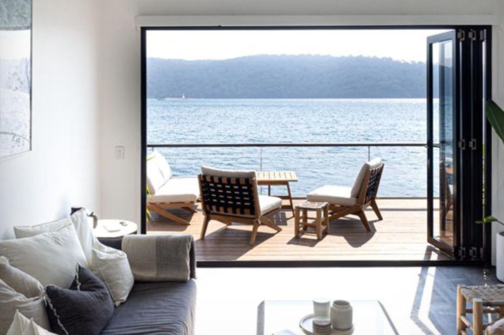 Intérieur d'une cabane, intérieur bois/blanc, ouverture vers l'eau et fauteuil sur la terrasse