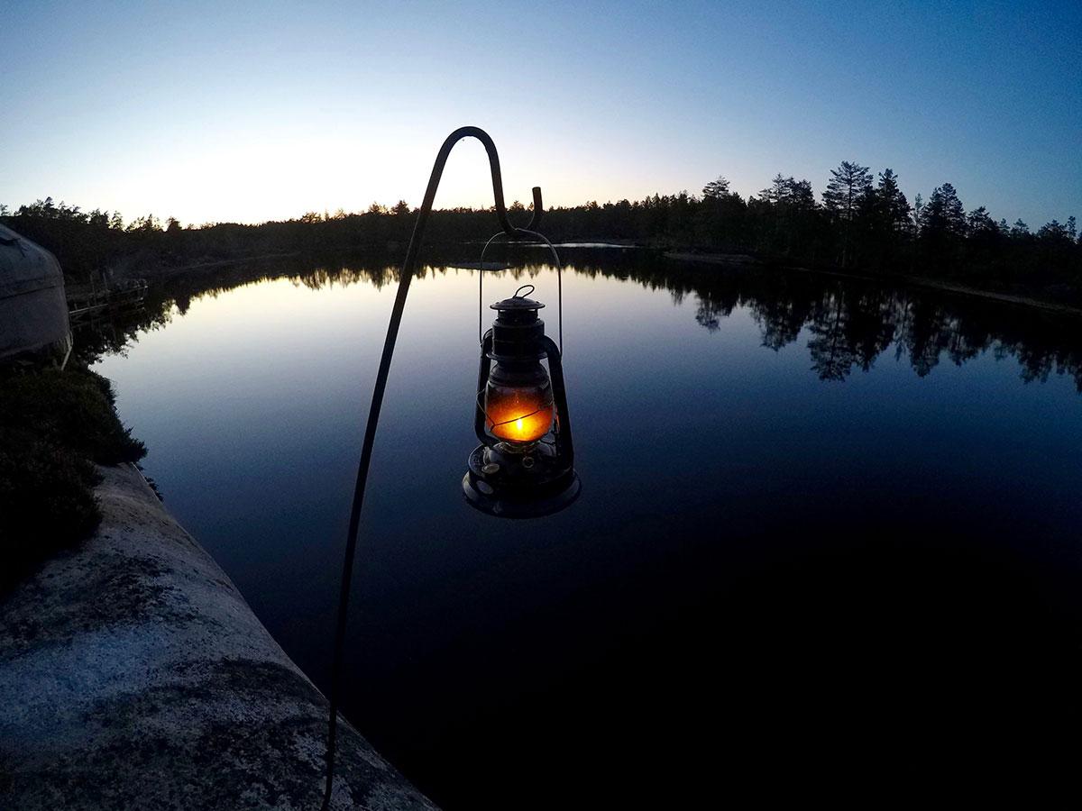 lanterne allumée dans un paysage nocturne, sur un lac