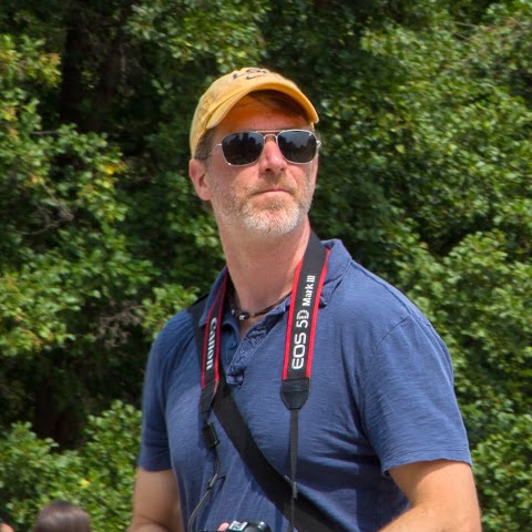 Brian Dean standing in front of trees looking skyward.