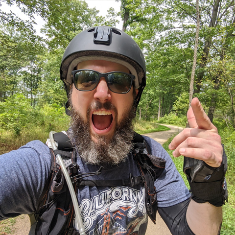 Kevin Koperski riding a OneWheel with a crazy beard.