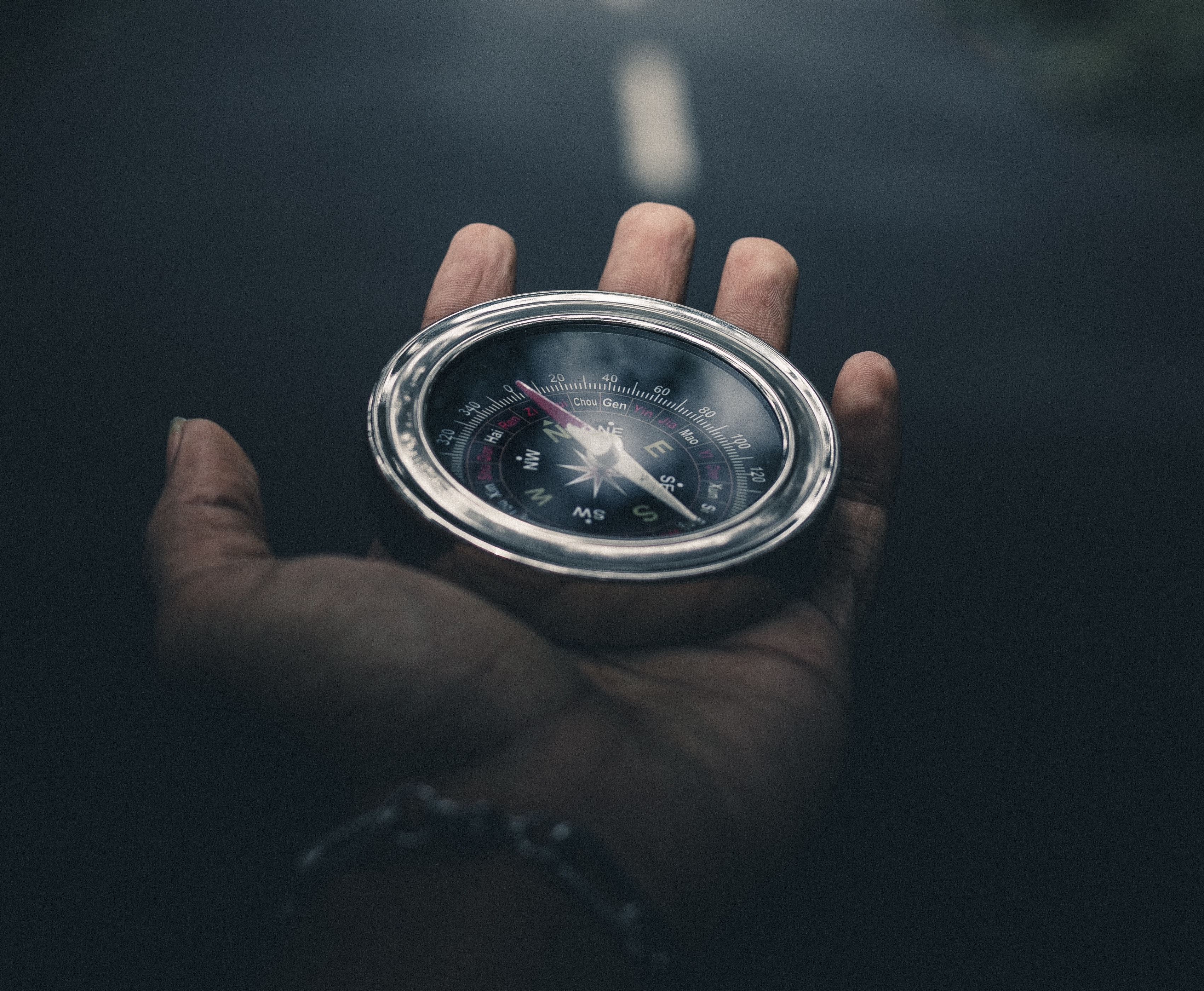 This picture shows a old-fashioned compass in a man's hand.