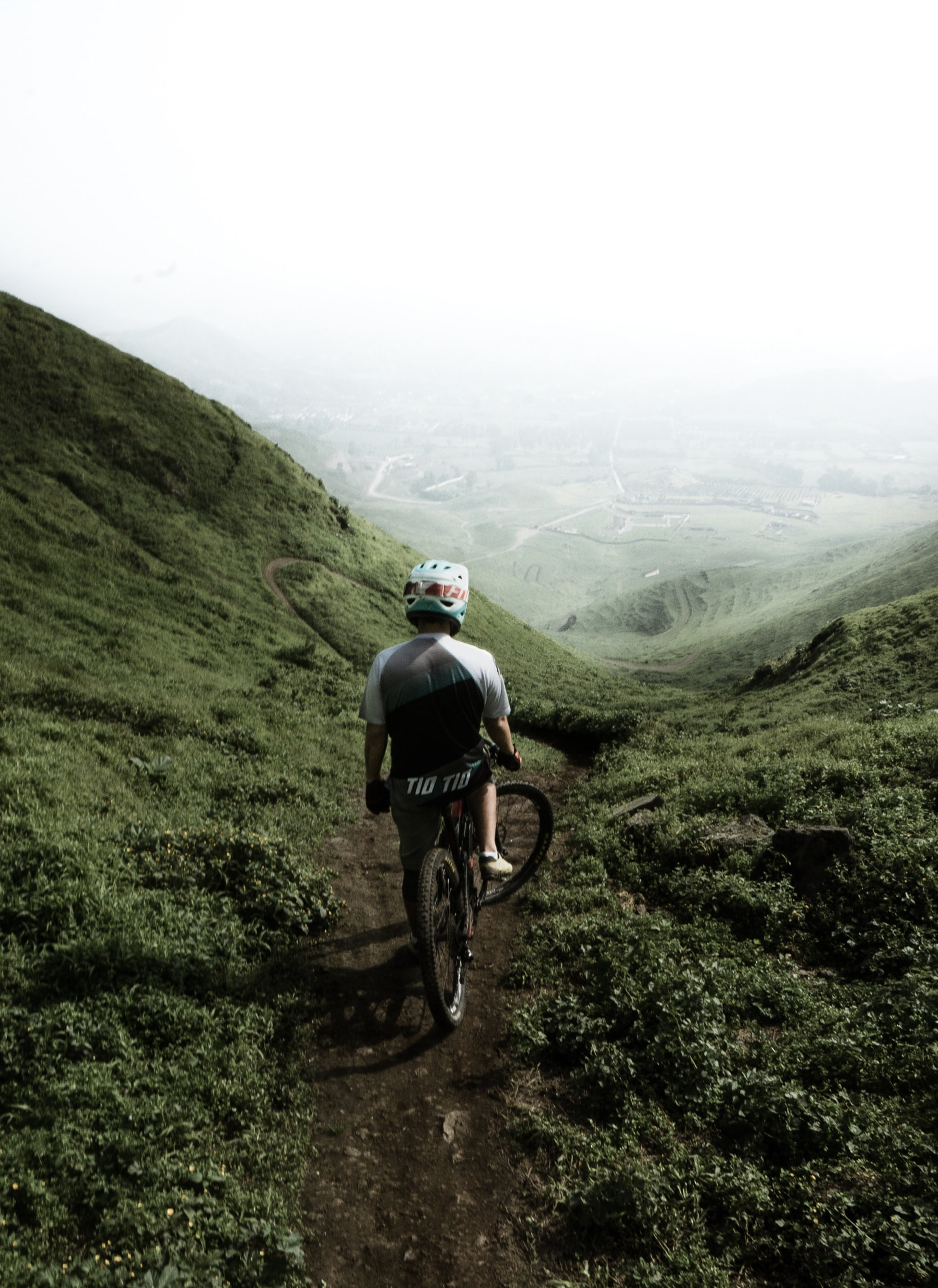This picture shows a mountain biker on top of a hill during foggy weather conditions.