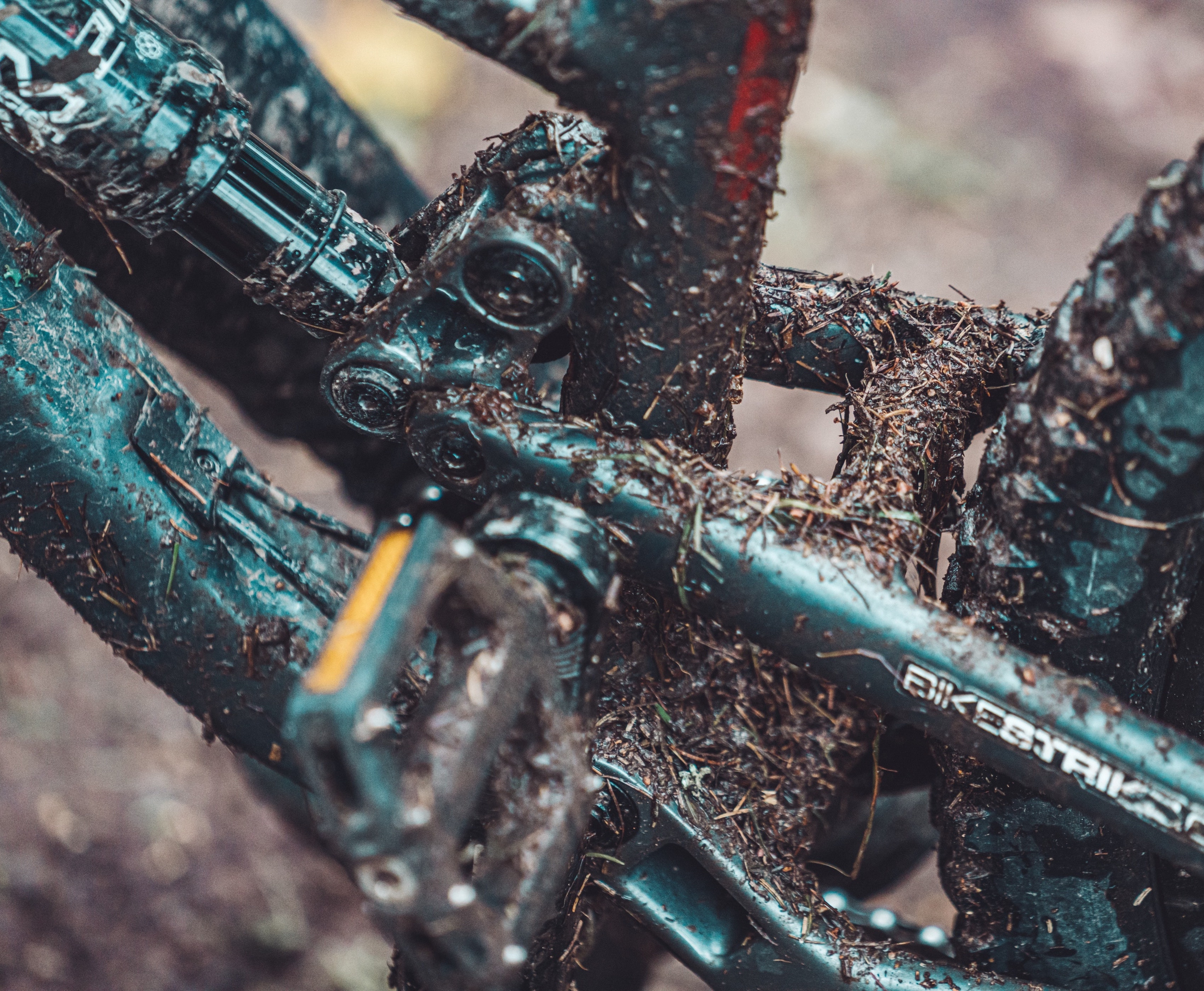 The picture shows a close-up of a dirty full suspension bike frame.