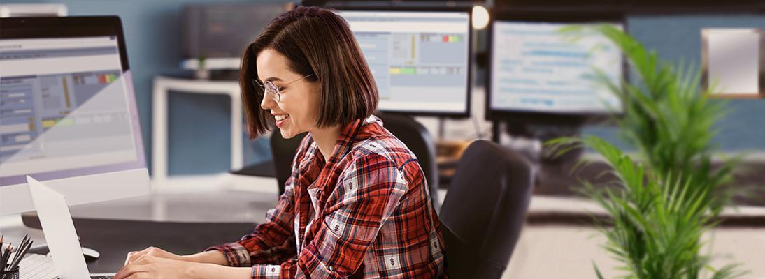 Junge Frau sitzt vor Laptop in einem Raum mit mehreren Monitoren auf welchen Libelle EDIMON läuft