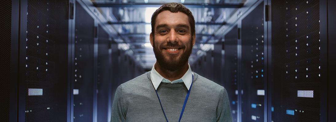 Lächelnder Mann steht in einem Serverraum
