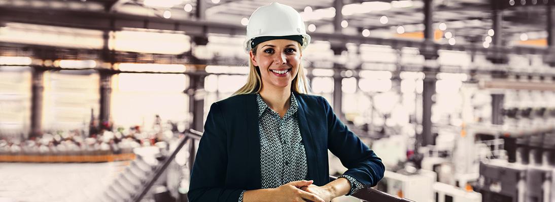 Lächelnde Frau in einem Fabrikgebäude